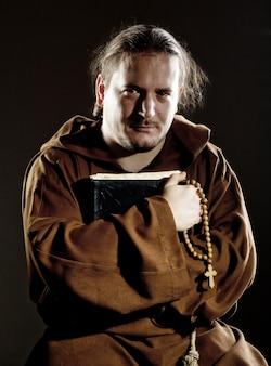 Mnich z biblią i różańcem
