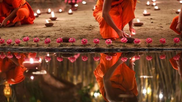 Mnisi siedzący w nocy medytują przy wielu świecach w tajskiej świątyni