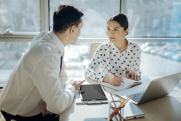 Mnogość pomysłów. piękna młoda kobieta siedzi przy stole obok swojego kolegi, robiąc notatki w swoim terminarzu podczas burzy mózgów