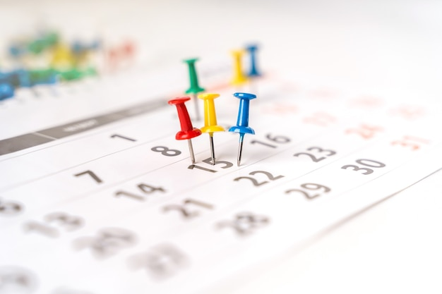 Mnóstwo kolorowych pinezek na zbliżeniu kalendarza. pojęcie planowania.