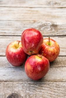 Mnóstwo pysznych i soczystych jabłek na drewnianym tle.