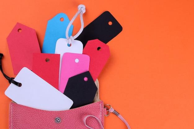Mnóstwo różnych metek i metek wypadających z różowego portfela. koncepcja czarny piątek. zakupy