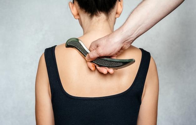 Mobilizacja tkanek miękkich wspomagana instrumentem, kobieta otrzymująca leczenie tkanek miękkich na plecach za pomocą narzędzia ze stali nierdzewnej iastm