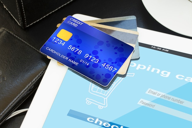 Mobilne zakupy - stos kart kredytowych z wirtualnym sklepem na ekranie tabletu