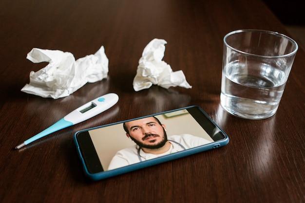 Mobilny ekran z lekarzem-mężczyzną online, chusteczkami, szklanką wody i termometrem na stole.