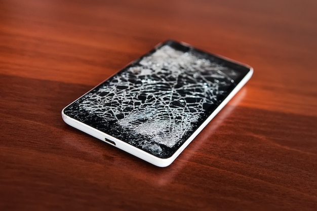 Mobilny smartfon z uszkodzonym ekranem. drewno w tle. koncepcja naprawy telefonu. stary zepsuty telefon z czarnym ekranem. wyświetlacz pękł w formie sieci.