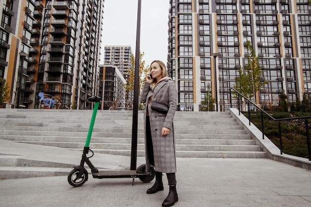 Mobilny transport publiczny. pewna siebie kobieta w jesiennym płaszczu rozmawiająca przy smartphonie i odwracająca wzrok. skutery elektryczne do publicznego udostępniania stojących na zewnątrz. nowoczesne bloki mieszkalne w tle.
