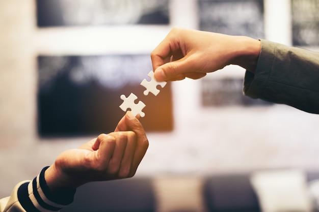 Moc strony ręka pełna ręka umieszczenie kawałka układanki do połączenia biznesu