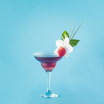 Mocktail ozdobiony kwiatem truskawki i tropikalnymi liśćmi