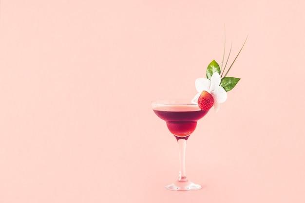 Mocktail ozdobiony truskawkami, kwiatami i liśćmi tropikalnymi, selektywnie skupiony.