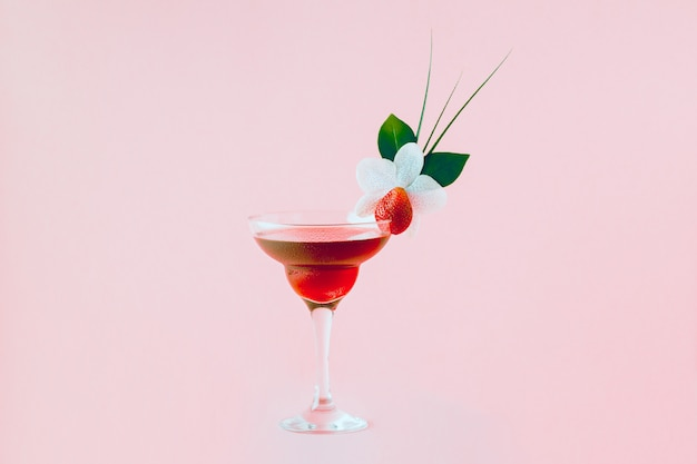 Mocktail ozdobiony truskawkami, kwiatami i tropikalnymi liśćmi