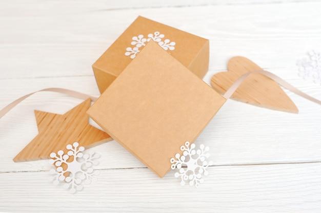 Mockup christmas gift boxes z drewnianą gwiazdą i sercem, z miejscem na tekst