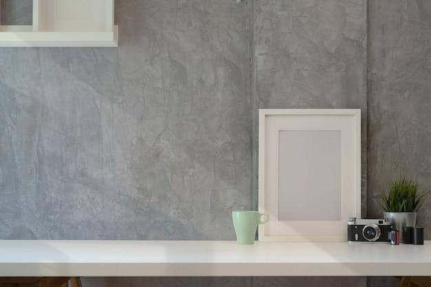 Mockup plakat z korzystną kamerą na białej drewnianej biurka przestrzeni i kopii przestrzeni.