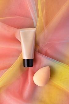 Mockup tonalny podkład cc lub bb kremowy podkład i gąbka do blendera na kolorowej tęczowej tkaninie z organzy. kosmetyczny płaski widok z góry