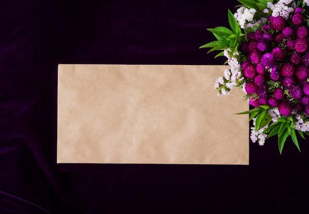 Mockup z papierową kopertą i kwiatem na ciemnym tle.