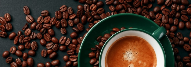 Mocna czarna kawa w kubku szmaragdowego koloru na czarnym matowym tle