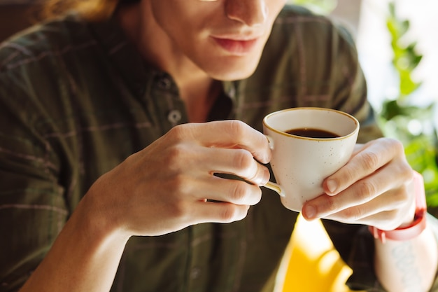 Mocna kawa. zbliżenie na filiżankę z mocną kawą będąc w męskich rękach