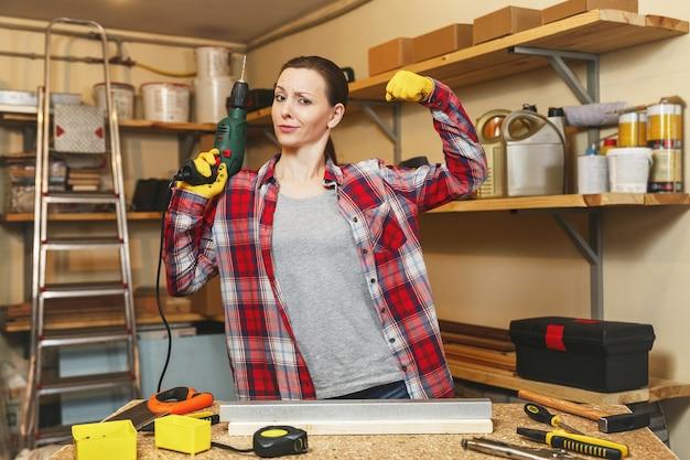 Mocna zabawa kaukaska młoda kobieta o brązowych włosach w kraciastej koszuli i szarej koszulce, pracująca w warsztacie stolarskim przy stole, wiercąc otworami w kawałku żelaza i drewna podczas robienia mebli.