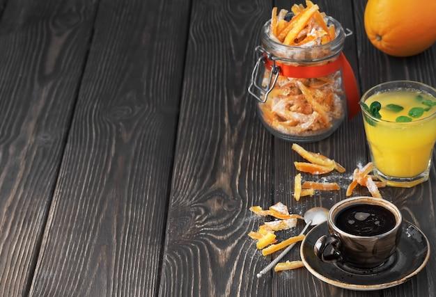 Mocne espresso, świeżo wyciśnięty sok pomarańczowy z liśćmi mięty i kandyzowanymi owocami w słoiku