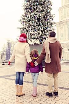 Mocne uczucia. śliczna dziewczyna krzyżuje nogi, stojąc między rodzicami