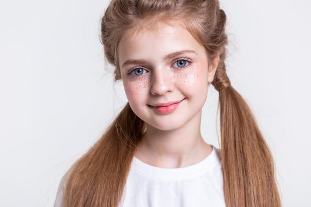 Mocne włosy. dość młoda modelka z długimi włosami o ciemnoniebieskich oczach uśmiecha się do kamery z różowymi ustami