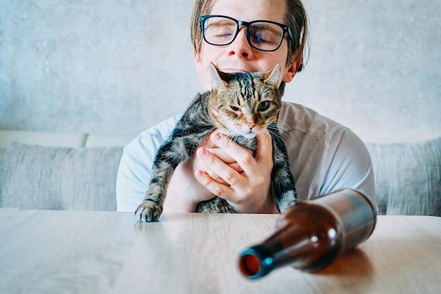 Mocno pijany mężczyzna przytula kota.