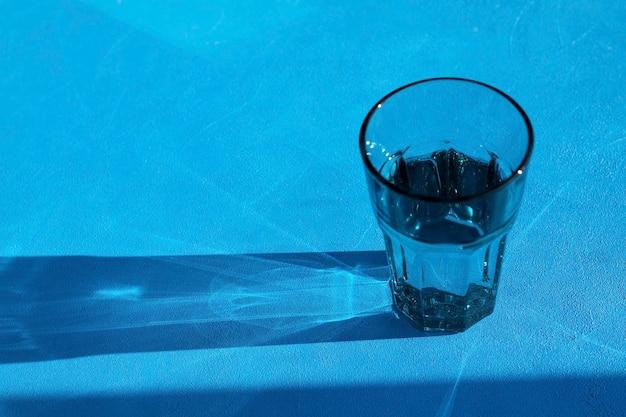 Mocny, abstrakcyjny cień z przezroczystej szklanki z wodą pitną.