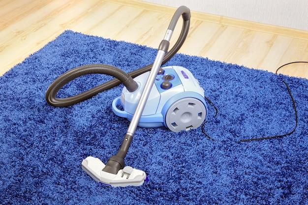 Mocny odkurzacz stojący na niebieskim dywanie.