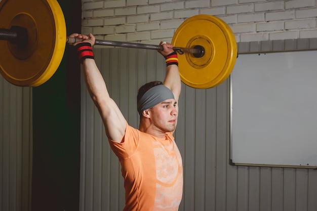 Mocny sportowiec crossfit w ciężkim, przysadzistym podnoszeniu w siłowni z napisem cross-fit box