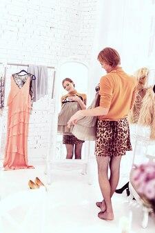 Mocowanie szarej sukienki. podekscytowana transseksualistka wybiera między szarą mini sukienką a spódniczką w panterkę, stylizując ją na czarną siateczkę