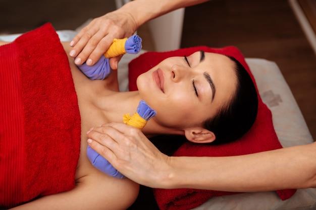 Mocowanie torebki ziołowej. uśmiechnięta kobieta z zamkniętymi oczami, zadowolona z niecodziennego zabiegu w profesjonalnym salonie spa
