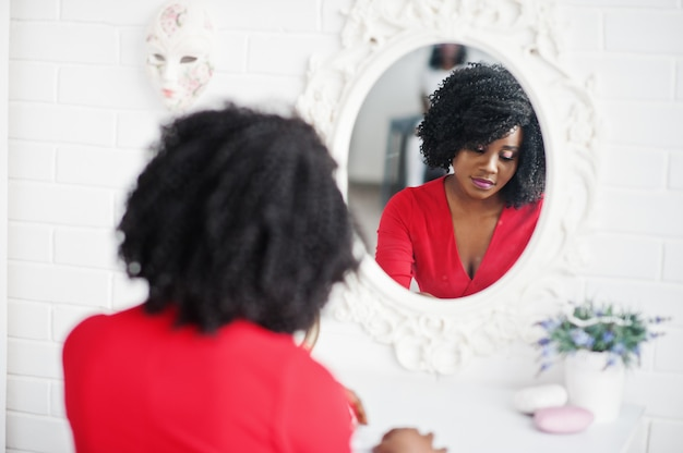 Moda african american model w czerwonej sukience piękna, seksowna kobieta, pozowanie suknia wieczorowa i patrząc w lustro.