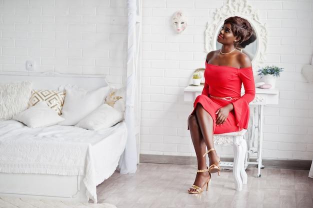 Moda amerykanina afrykańskiego pochodzenia model w czerwonej piękno sukni, seksowna kobieta pozuje sukni wieczorowej obsiadanie przy krzesłem przeciw lustrze w białym rocznika pokoju.