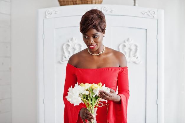 Moda amerykanina afrykańskiego pochodzenia model w czerwonej piękno sukni, seksowna kobieta pozuje sukni wieczorowej trzyma kwiaty w białym rocznika pokoju.
