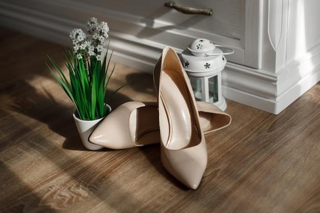Moda beżowe buty na wysokich obcasach na białym tle na drewnianej podłodze. para klasycznych butów damskich na obcasach.