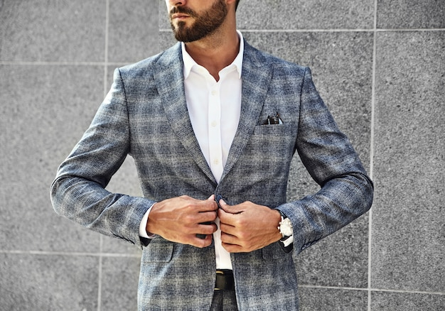 Moda biznesmena model ubierał w eleganckim w kratkę kostiumu pozuje blisko szarości ściany na ulicznym tle. metroseksualny z luksusowym zegarkiem na nadgarstku