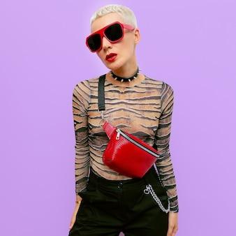 Moda blond lady tomboy luksusowy styl. stylowe akcesoria. kopertówka i okulary przeciwsłoneczne