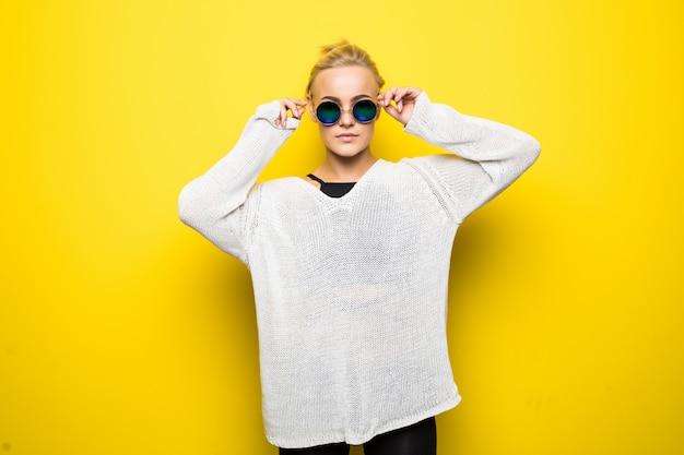 Moda blondynka w nowoczesny biały sweter w genialnych niebieskich okularach przeciwsłonecznych pozuje na żółto