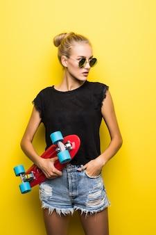 Moda całkiem fajna dziewczyna w okularach przeciwsłonecznych z deskorolką na kolorowym żółtym tle