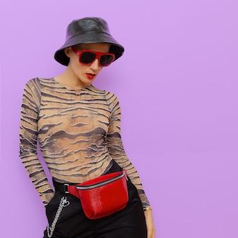 Moda cute swag girl stylowe dodatki. kopertówka, okulary przeciwsłoneczne i czapka panama
