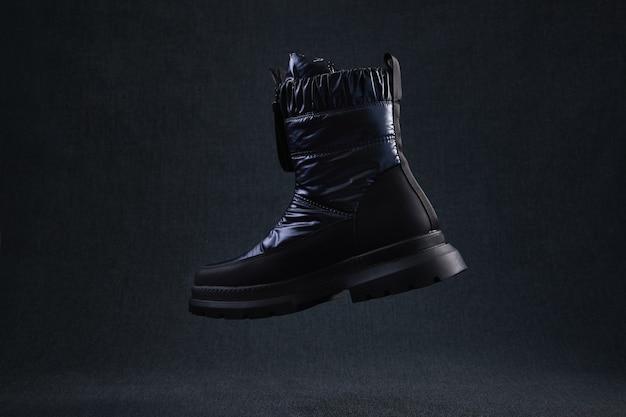 Moda czarny niemarkowy but latający na ciemnym tle. czarne buty do wędrówek zimowych lewitują w powietrzu. nowoczesne stylowe damskie buty do chodzenia po bezdrożach.