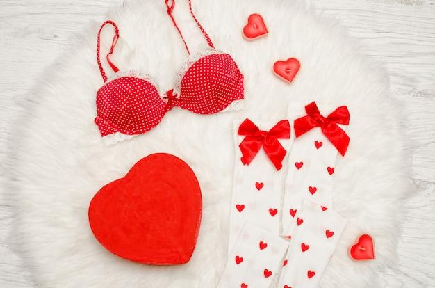 Moda. czerwone pudełko w kształcie serca z koronkową bielizną, białe pończochy z kokardkami, czerwony stanik, czerwone świece w kształcie serca na białym futrze.