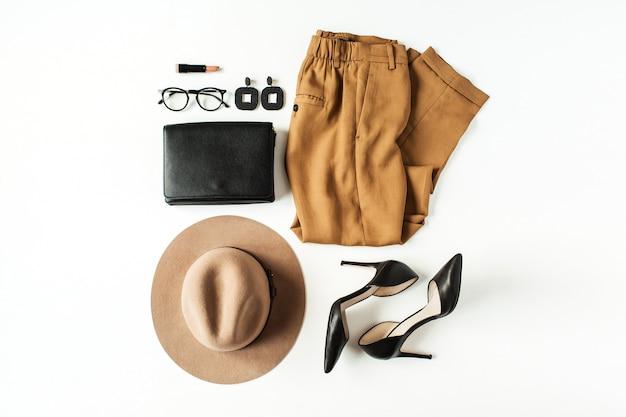 Moda damska odzież, akcesoria na białym tle. płaski kolaż, widok z góry, minimalny modny styl życia. spodnie, buty na obcasie, okulary, czapka, torebka, kolczyki