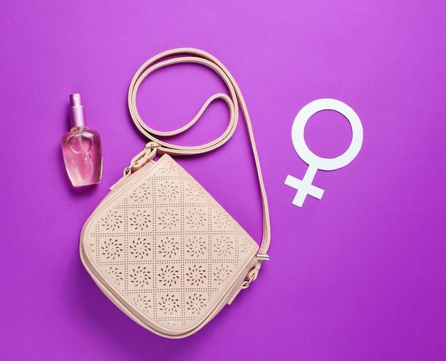 Moda damska torba, butelka perfum, symbol feminizmu płci na fioletowym tle.