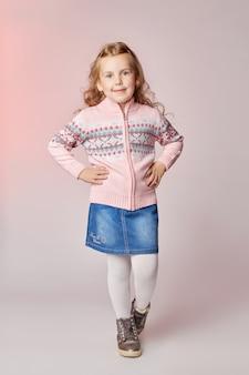 Moda dla dzieci młodych modeli dzieci pozuje do aparatu. rudowłosa dziewczyna się uśmiecha