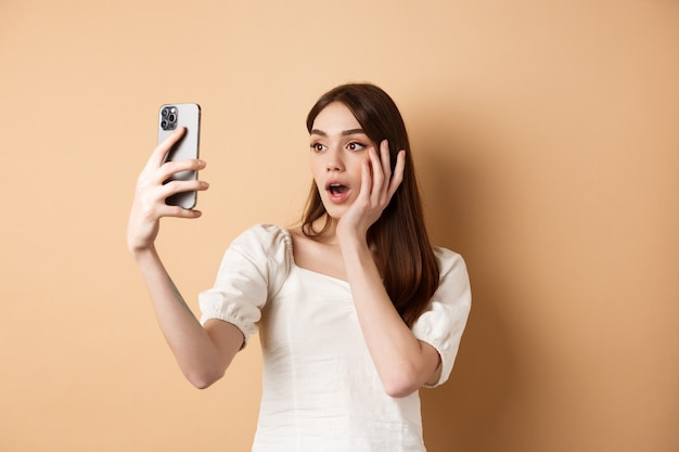 Moda dziewczyna nagrywa blog na smartfonie biorąc selfie na telefon stojący na beżowym tle