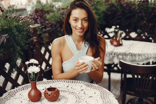 Moda dziewczyna pije kawę w kawiarni