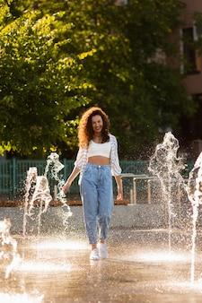 Moda dziewczyna pozuje otoczona fontanną