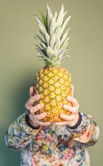 Moda dziewczyna trzyma ananasa przed twarzą