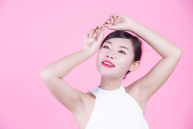 Moda dziewczyna ubierać się za pomocą gestów na różowym tle.